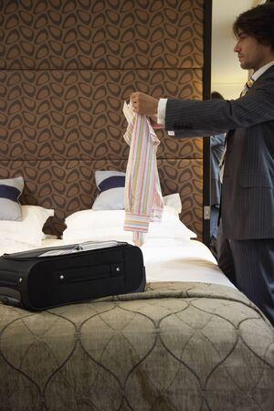 bedspread: Businessman Folding Shirt in Hotel Room