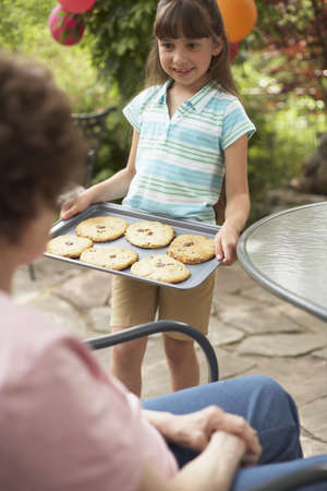 jewish home: Granddaughter Showing Grandmother Tray of Homemade Cookies