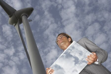 environmental issues: Businessman with Mirror by Wind Turbine LANG_EVOIMAGES