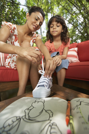 family sofa: Mother Helping Daughter Tie Shoes LANG_EVOIMAGES