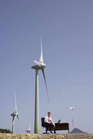 Man Sitting at Desk by Wind Farm