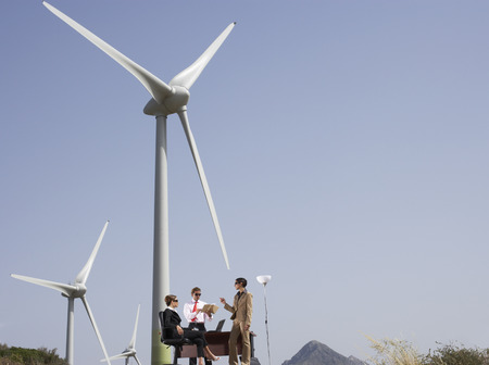 Business People around Desk at Wind Farm