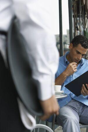 Man Reading Menu at Cafe