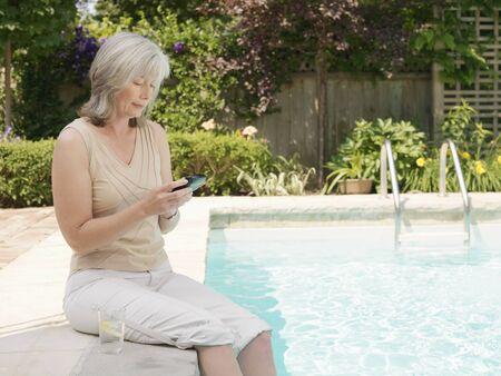 Woman at Side of Pool Looking at PDA