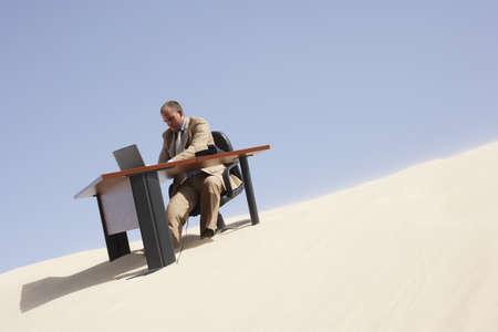 Businessman at Desk at Top of Sand Dune