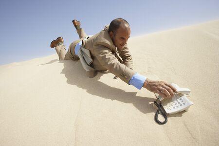Businessman Reaching for Telephone in Desert