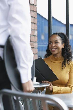 sidewalk talk: Woman Talking to Waiter at Cafe