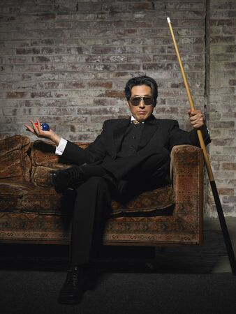 nightspot: Portrait of Man on Sofa with Pool Cue and Billiard Balls LANG_EVOIMAGES
