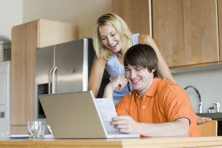 electronic commerce: Couple in Kitchen with Laptop Computer LANG_EVOIMAGES