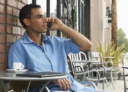 sidewalk talk: Man sitting at Cafe Table and Talking on Cellular Phone
