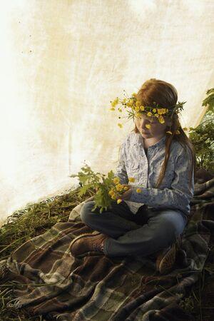 Chica jugando al aire libre con flores silvestres