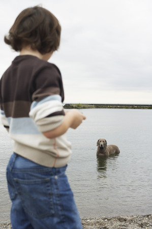 wetting: Boy Looking at Dog in Lake