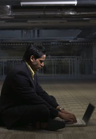 Man Sitting on Office Floor, Using Laptop Computer