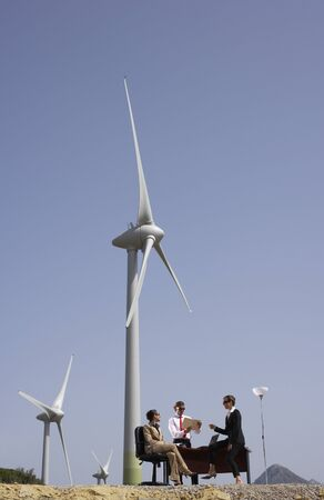 Business People around Desk by Wind Farm
