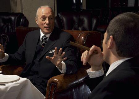 elite: Men Chatting and Smoking Cigars