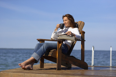 Woman Relaxing on Dock by Water