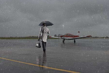 salespeople: Backview of Businessman Walking on Tarmac in Rainy Weather