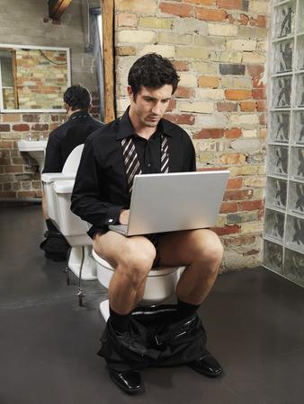 homeoffice: Man Sitting on Toilet Using Laptop Computer