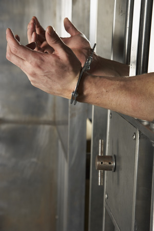 Man Handcuffed to Cell Door LANG_EVOIMAGES