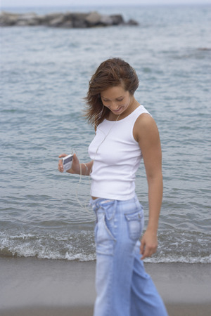 oceanic: Woman Walking along Beach with MP3 Player