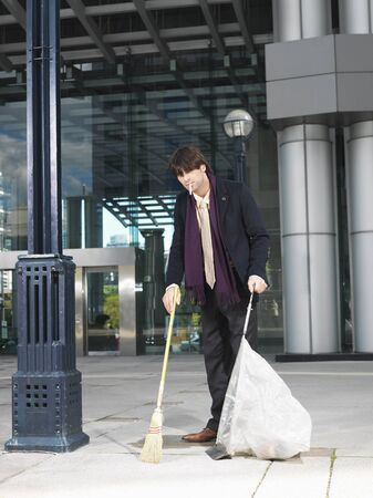 street lamp: Man Sweeping Up Outside Building