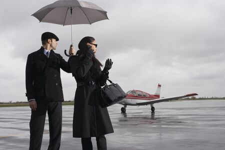 wetting: Man and Woman on Airport Tarmac LANG_EVOIMAGES