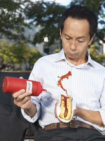 Man with Hot Dog Squirting Ketchup on Shirt LANG_EVOIMAGES