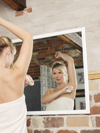 woman mirror: Woman Applying Deodorant
