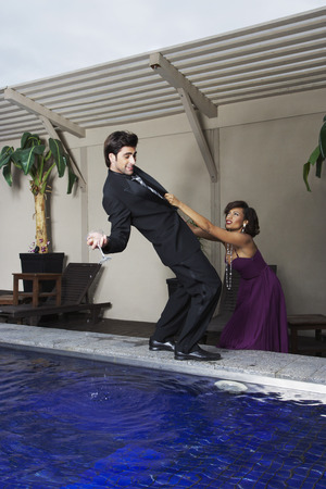 nightspot: Woman Holding onto Man Losing Balance at the Side of Pool LANG_EVOIMAGES