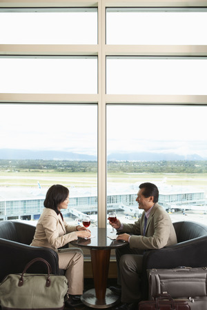 window view: Couple Toasting in Airport, Vancouver, British Columbia, Canada LANG_EVOIMAGES