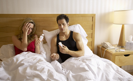 Couple in Bed, Woman Taking Pills LANG_EVOIMAGES