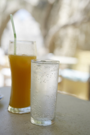 seltzer: Glasses of Juice and Water on Cafe Table