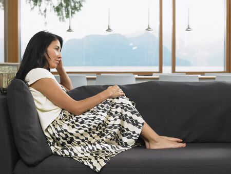window view: Woman Sitting on Sofa at Home