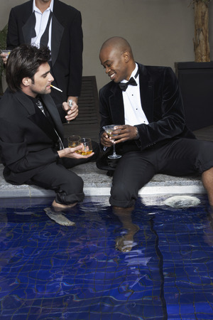 spot: Men in Tuxedos with Feet in Pool Drinking Cocktails