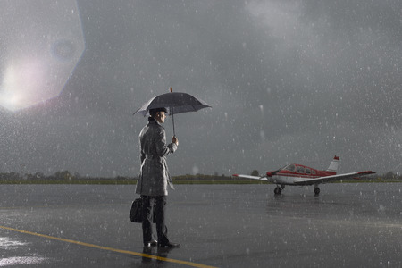 Businessman Standing on Tarmac in Rainy Weather