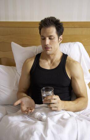 Man in Bed, Taking Pills