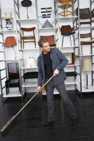 the footstool: Man Sweeping Up in Furniture Store