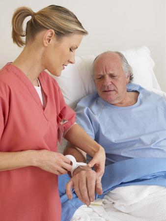 Nurse Administering Intravenous to Patient LANG_EVOIMAGES