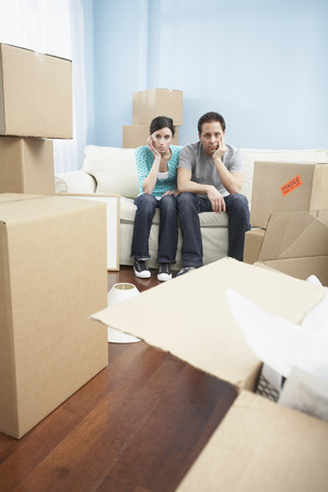 moving box: Couple Sitting on Sofa in New Home LANG_EVOIMAGES