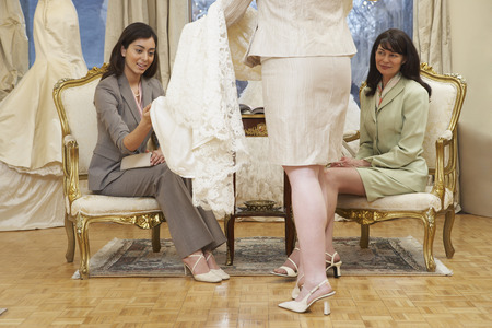 salespeople: Women in Bridal Boutique Looking at Wedding Gown