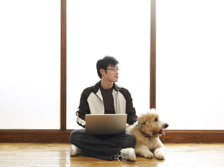 Man Sitting on Floor Using Laptop