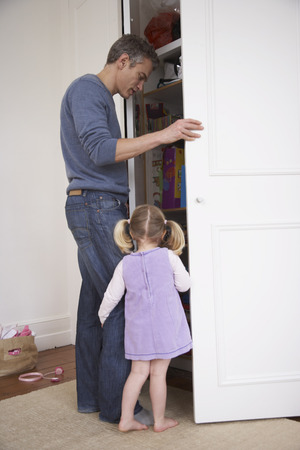 Father and Daughter Looking in Closet