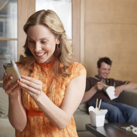 Woman Using Cellular Phone, Man in Background LANG_EVOIMAGES