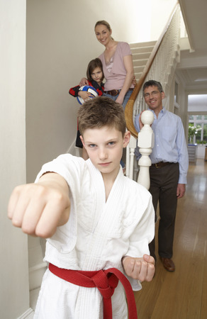 brotherly love: Boy in Karate Gi With Family in Background