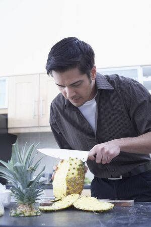 counter top: Man Peeling Pineapple LANG_EVOIMAGES