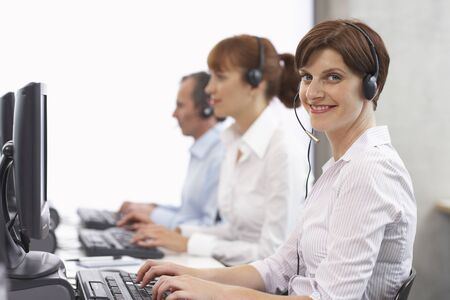 Business People Working on Computers with Headsets LANG_EVOIMAGES