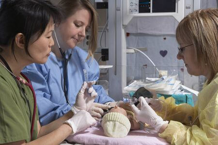 surgical department: Nurses Practicing on Baby Mannequin LANG_EVOIMAGES