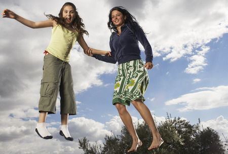 wind blown hair: Mother and Daughter Jumping LANG_EVOIMAGES