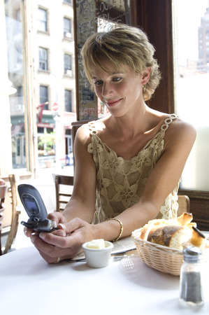 Woman Using Cellular Phone in Cafe
