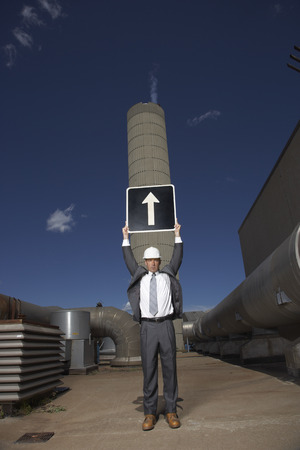 environmental issues: Businessman Holding Arrow Sign Outside Factory LANG_EVOIMAGES